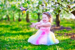 Child playing with a bird. Happy laughing little girl in fairy costume with wings feeding a pet parrot in a cherry tree garden. Kid having fun in blooming fruit orchard in spring. Kids gardening.
