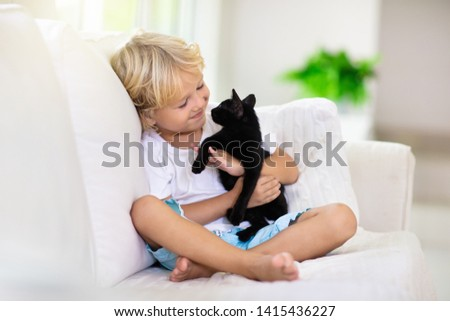 Child playing with baby cat. Kid holding black kitten. Little boy snuggling cute pet animal sitting on white couch in sunny living room at home. Kids play with pets. Children and domestic animals. #1415436227