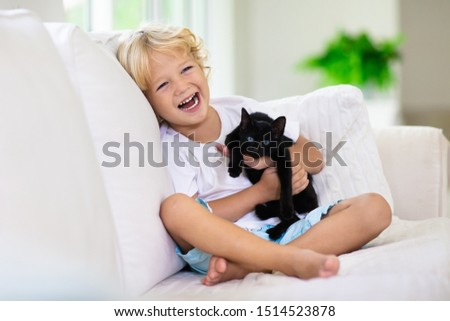 Child playing with baby cat. Kid holding black kitten. Little boy snuggling cute pet animal sitting on white couch in sunny living room at home. Kids play with pets. Children and domestic animals. #1514523878