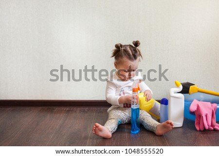 child playing with bottles with household chemicals sitting on the floor of the house #1048555520