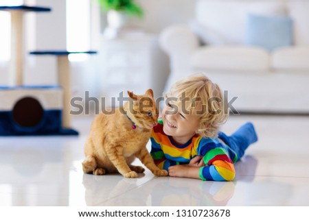 Child playing with cat at home. Kids and pets. Little boy feeding and petting cute ginger color cat. Cats tree and scratcher in living room interior. Children play and feed kitten. Home animals. #1310723678