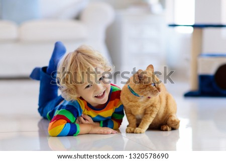Child playing with cat at home. Kids and pets. Little boy feeding and petting cute ginger color cat. Cats tree and scratcher in living room interior. Children play and feed kitten. Home animals. #1320578690