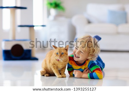 Child playing with cat at home. Kids and pets. Little boy feeding and petting cute ginger color cat. Cats tree and scratcher in living room interior. Children play and feed kitten. Home animals.