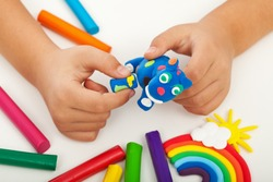 Child playing with colorful clay making animal figures - closeup on hands