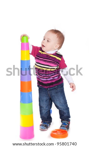 Child playing with colorful pyramid, isolated