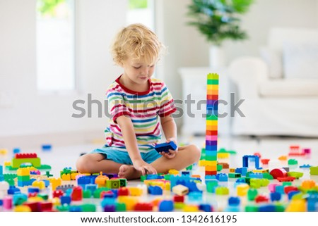 Child playing with colorful toy blocks. Little boy building tower at home or day care. Educational toys for young children. Construction block for baby or toddler kid. Mess in kindergarten play room. #1342616195