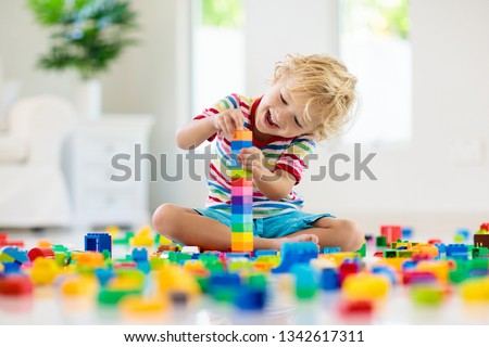 Child playing with colorful toy blocks. Little boy building tower at home or day care. Educational toys for young children. Construction block for baby or toddler kid. Mess in kindergarten play room. #1342617311