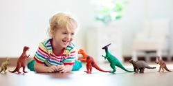 Child playing with colorful toy dinosaurs. Educational toys for kids. Little boy learning fossils and reptiles. Children play with dinosaur toys. Evolution and paleontology game for young kid.