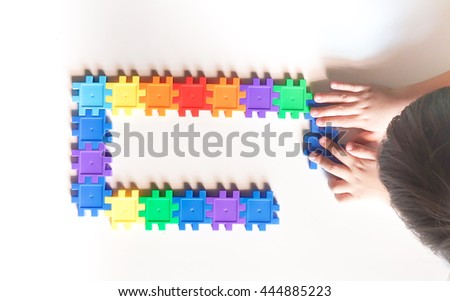 Child playing with colorful toy puzzle #444885223