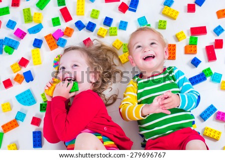 Child playing with colorful toys. Little girl and baby boy with educational toy blocks. Children play at day care or preschool. Mess in kids room. View from above.