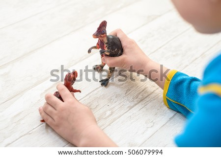 child playing with dinosaurs