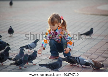Child playing with doves in the city street
