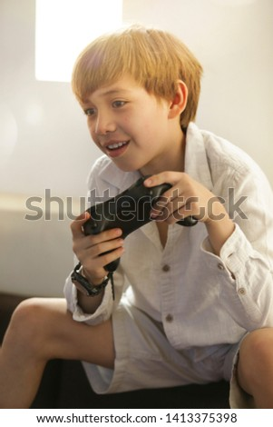 child playing with gamepad, with different poses, excited, angry, frustrated, happy, sad. Addict to the video game. Video game   #1413375398