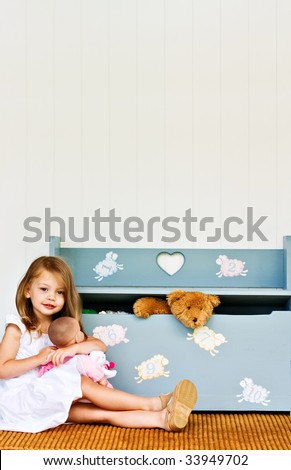 Child playing with her doll while a teddy bear pokes his head out of a toy chest.