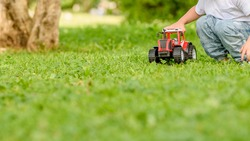 Child playing with red toy car on the grass outdoors in the park. Selective focus. Banner.
