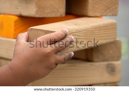 Child playing with the wood game (jenga) in the beach