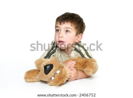 Child playing with toy.  Child dressed in casual clothes,  laying on the floor holds closely a plush toy dog.  He is looking up, space for text.