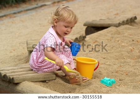 Child playing with toys in a sandbox