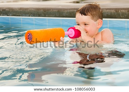 Child playing with water gun while swimming in pool during summer