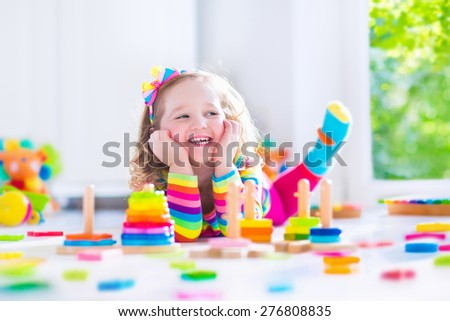 Child playing with wooden toys at preschool. Cute toddler girl having fun with toy blocks, building a tower at home or day care. Educational kids toy for nursery or kindergarten.