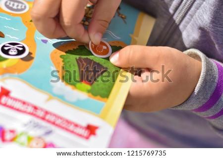 Child plays a pirate quest on a paper map, hands glue a sticker #1215769735