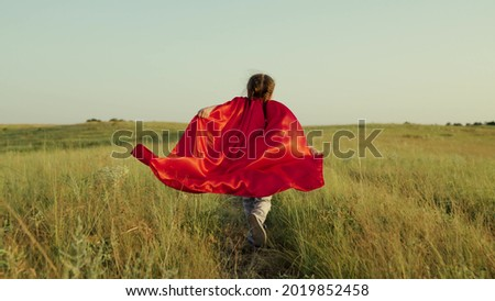 Child plays and dreams. Happy superhero girl, runs on green field in red cloak, cloak flutters in wind. Teenager dreams of becoming superhero. Young girl in red cloak, dream expression.