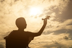 child plays with a toy airplane in the sunset and dreams of journey.silhouette young boy holding toy,hand holding small plane close up.vintage tone