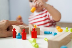 child plays with developmental toy. boy plays with wooden cylinders and sorting by size. The concept of educational toys. development of fine motor skills, imagination and logical thinking