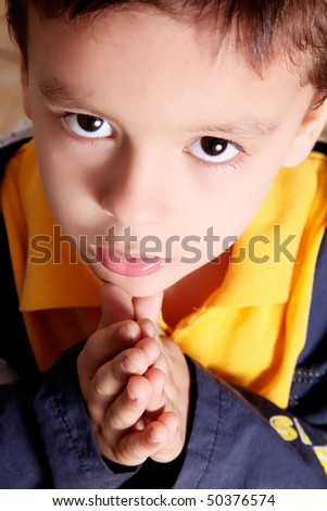 Child praying  and looking up with blue and yellow jacket