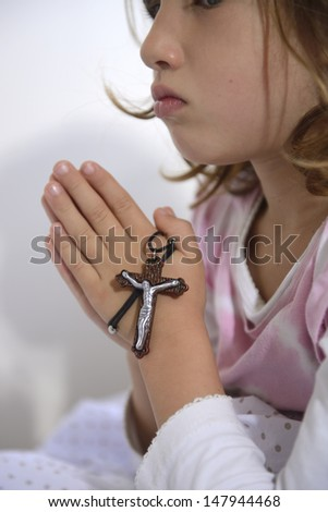 child praying to god with rosary