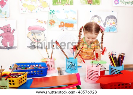 Child preschooler with colour pencil in play room.