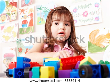 Child preschooler with construction set in play room.