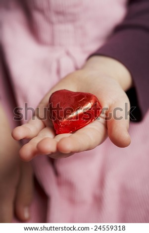 child presenting a red candy heart