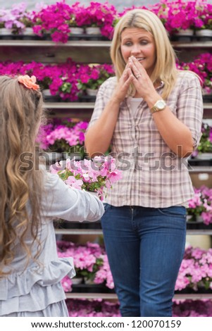 Child presenting flowers to her surprised mother in garden center
