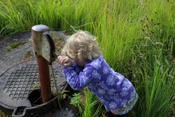 child presses on the tap hand pump