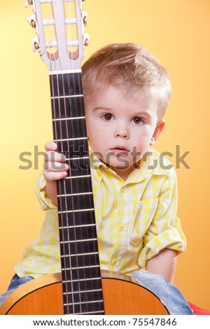 Child proposing play the guitar looking at camera