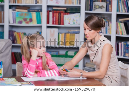 Child psychologist with a little girl, a child draws with colored pencils