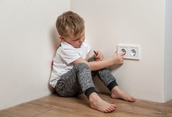 Child put finger in socket.  Dangerous situation at home. Child playing with electrical socket.