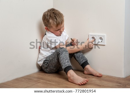 Child put finger in socket.  Dangerous situation at home. Child playing with electrical socket. #772801954