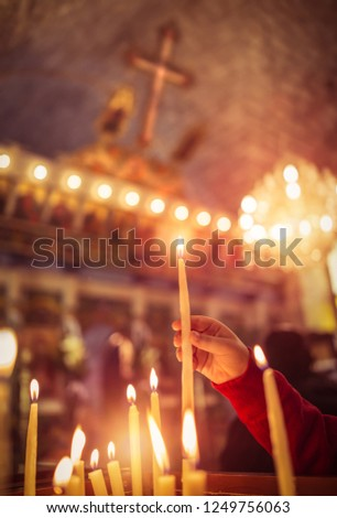 Child puts a candle in the church, praying with faith, traditional visit of a holy place for Easter, great Christian holiday, belief in God concept