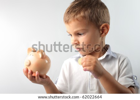 child putting a money in his piggy-bank