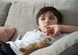 Child putting finger in his mouth.Schoolboy biting his finger nails while watching TV, Emotional kid portrait, Young boy siting on sofa looking out with thinking face or nervous, Children Health care