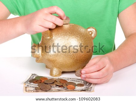 child putting money in a golden piggy bank