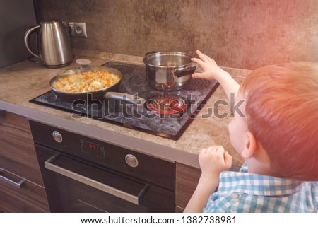 Child reaches for the hot electric stove. Child safety at the stove.