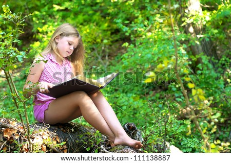 Child reading a book in the park