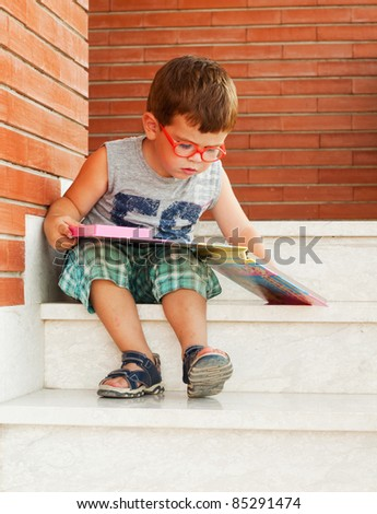 Child reading a book sitting on the stairs