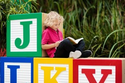 Child reading book in school yard. Kid learning abc letters. Little boy sitting on wooden toy blocks with alphabet in preschool or kindergarten. Kids read books. Children learn and study.