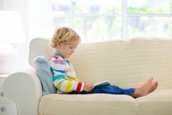 Child reading book. Kids read books. Little boy sitting on white couch in sunny living room watching pictures in story book. Kid doing homework for elementary school or kindergarten. Children study.