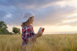 Child reading book or bible outdoors . Cute little girl reading the Bible . Young Child's Hands Praying on Holy Bible