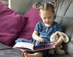Child reading. Little cute girl 1-3 is reading a book with a toy plush hare sitting on a sofa